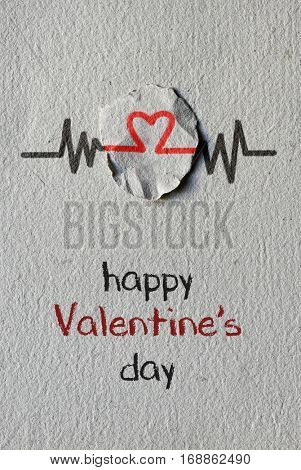 a red heart symbol on a round piece of paper as in an electrocardiogram and the text happy valentines day written on a textured paper background