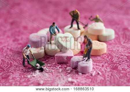 Man carrying a candy heart with for you print on it.  A man with broken heart in front of him.