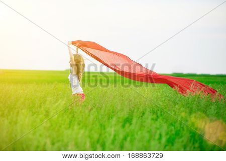 Young lady runing with tissue in green field. Beautiful happy woman walking  in the summer rural meadow. Outdoor summer portrait of pretty sport style woman jumping with fabric. Beautiful fit tan girl. Sexy slim model caucasian ethnicity outdoors.