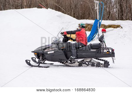 February 4 2017. Close-up of a paramedic riding on a snowmobile to the site of a snowboarding accident. Gokase Ski Area Miyazaki Japan.