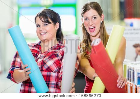 Young women in home improvement store choosing wallpapers for DIY renovating project