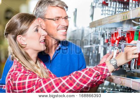 Young woman asking shop assistant in ironware department of hardware store about mountings for window boxes