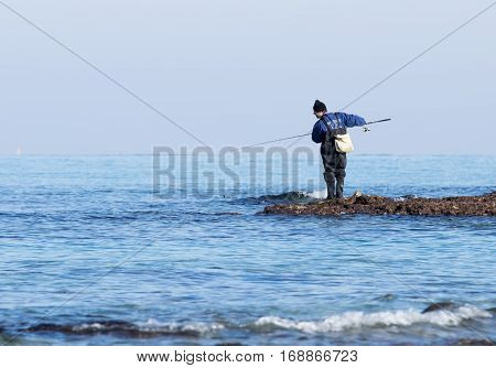 Fisherman Catches A Fish On A Spinning At Winter Morning