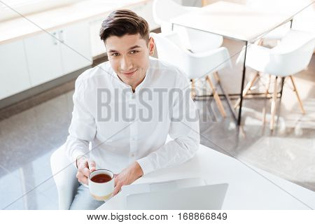 Photo of cheerful man dressed in white shirt using laptop computer while drinking coffee. Coworking. Looking at camera.