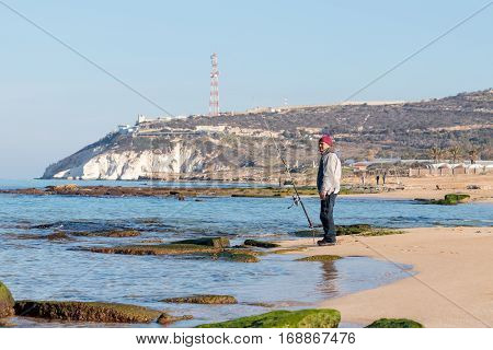 Rosh Hanikra Israel - February 04 2017 : Fisherman catches a fish on a spinning at winter morning on the beach near the Rosh Hanikra Israel