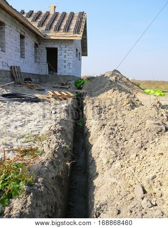Trench for sewer pipes during house construction. Trench for Sanitary Sewer Pipe in the New House Construction
