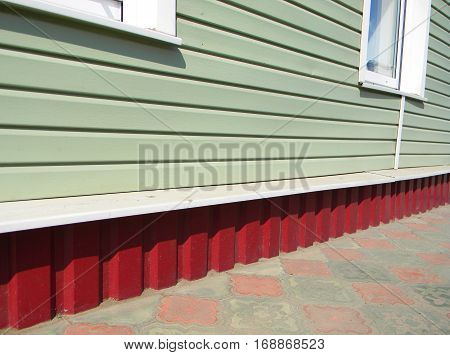 Renovation house with new plastic siding walls and metal profil foundation waterprofing.
