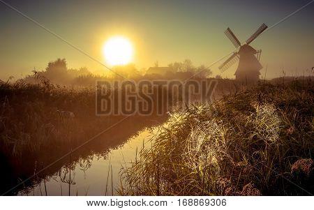 Dutch Windmill In Marshland With Cobwebs