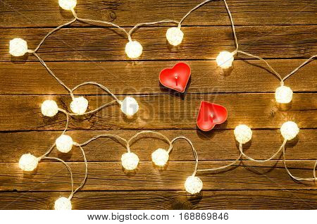 Two candles in the shape of heart among the glowing lanterns made of rattan on a wooden background. View from above