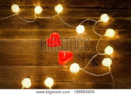 Two red candles in the shape of a heart and glowing lanterns made of rattan on a wooden background. Top view space for text