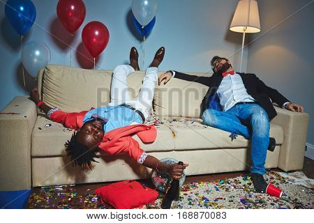 Tired guys sleeping on couch after tiresome party