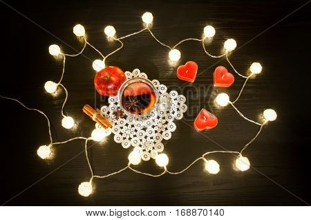 Candles in the shape of a heart mulled wine with spices on a lacy napkin cinnamon and apple. Rattan lanterns on black wooden table top view