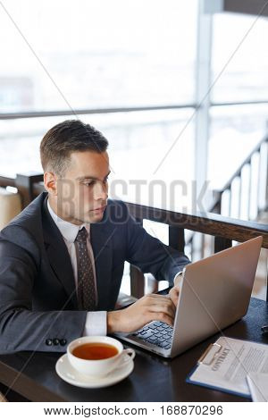 Young trader with laptop looking for information online