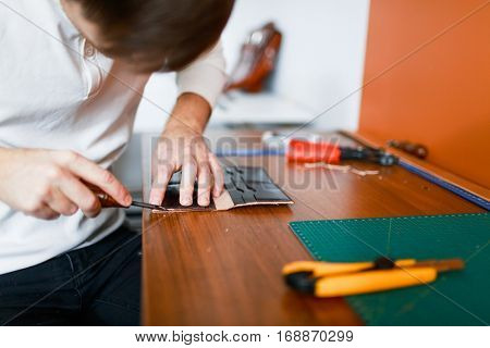 Craftsman making leather wallet in his workshop