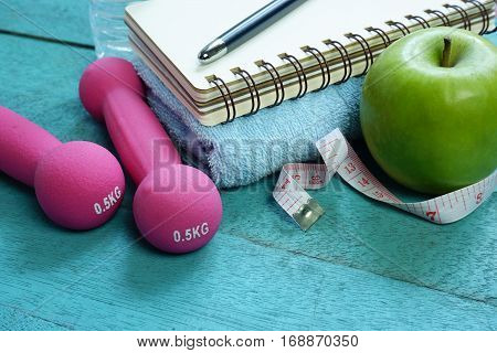 Fitness equipment. Nutrition food, notebook on turquoise wooden background.