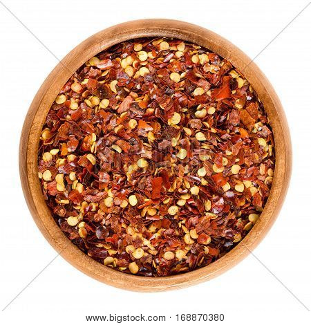 Dried chili pepper flakes in wooden bowl. Dried and crushed fruits of Capsicum frutescens, used as hot spice and for tabasco sauce. Isolated macro food photo close up from above on white background. poster