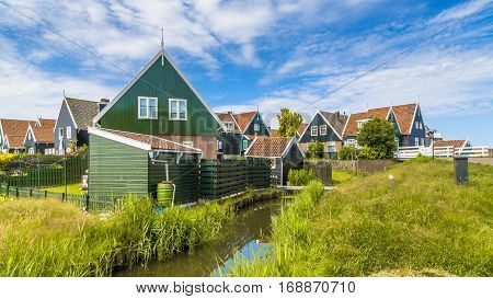 Traditional Dutch Fishing Village Scene With Wooden Houses And Canal