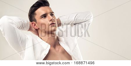 Fashion portrait of a handsome man with trendy hairstyle in a white shirt. Young man thought and dreams.