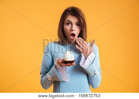 Amazed astonished young woman holding cake on her palm