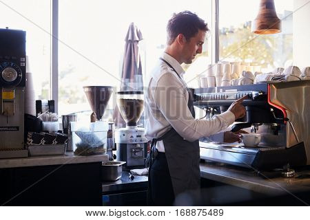 Barista Making Coffee In Delicatessen Using Machine