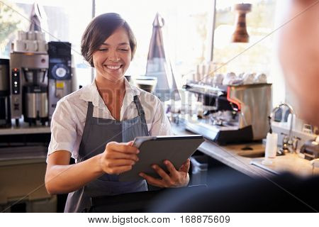 Cashier Takes Card Payment From Customer With Digital Tablet