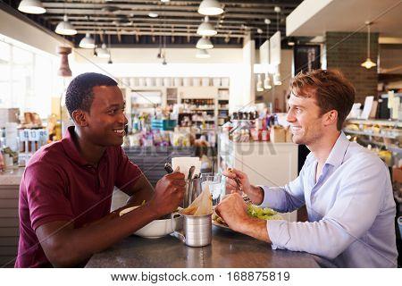 Two Men Enjoying Lunch In Delicatessen Restaurant