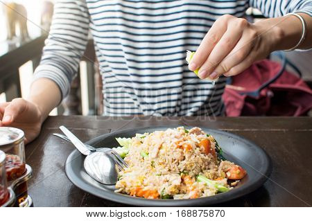 Female Hand Squeezing Lime On Fried Rice