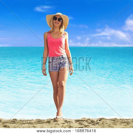 Young blonde woman walking on the beach wearing sun glasses and hat.