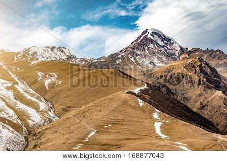 Ridge, dotted with forests and fields, stretches underneath a lonely snow-capped mountain , Georgia