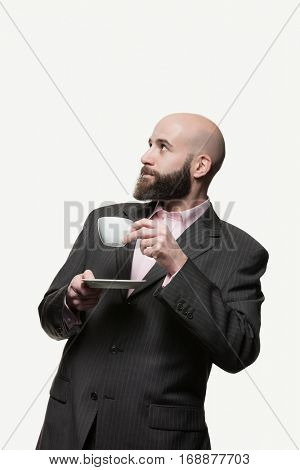 Young bald man with a beard drinks a cup of coffee looking up