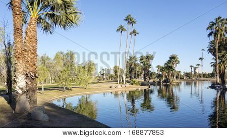 Bright and clear winter sky reflecting in deep blue water of Encanto park lake Phoenix downtown Arizona