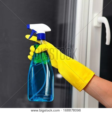 Hand in yellow glove holding spray for cleaning window