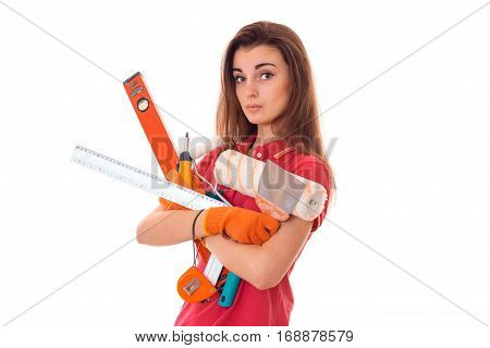young charming builder girl in uniform makes renovation isolated on white