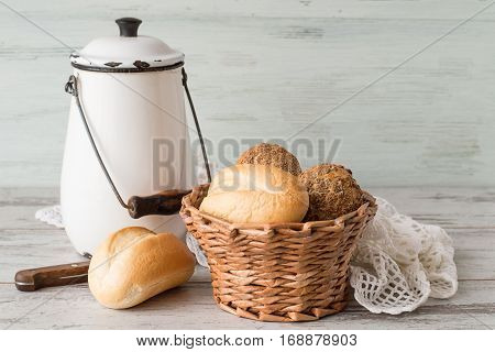 Breakfast. A wicker basket with fresh bread, a can of milk and a openwork white napkin on a light wooden table.