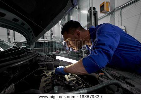 car service, repair, maintenance and people concept - auto mechanic man with lamp working at workshop