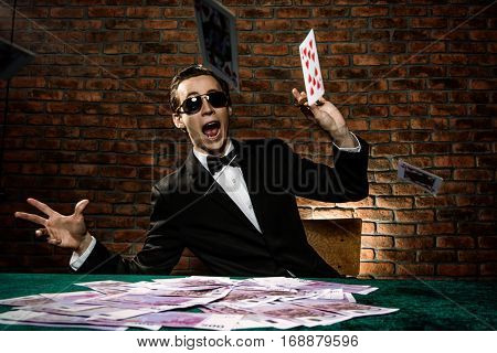 The gambler man throwing cards on the game table. Big cash prize, the jackpot.
