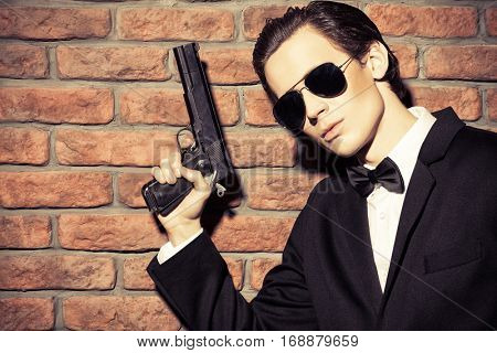 Handsome man in black suit and sunglasses holding a gun. Secret agent, mafia.