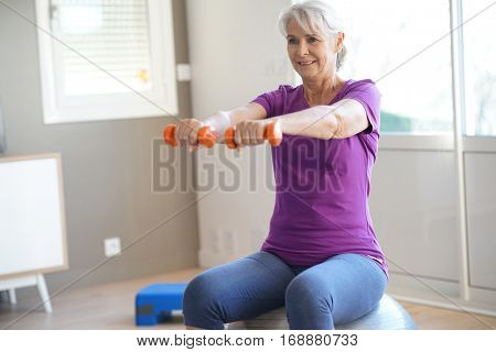 Senior woman doing fitness exercices in front of tv
