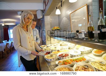 Senior woman helping herself from delicatessen buffet