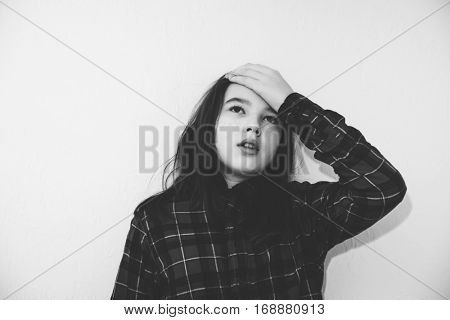 Black and white portrait of a teenage girl with a headache. Vintage style