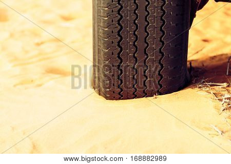 an SUV's flattened tire on a sand dune