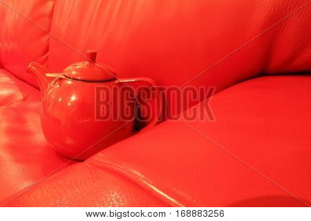 deep red tea pot on red couch