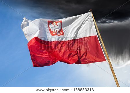 Polish national flag on dramatic sky with downpour.