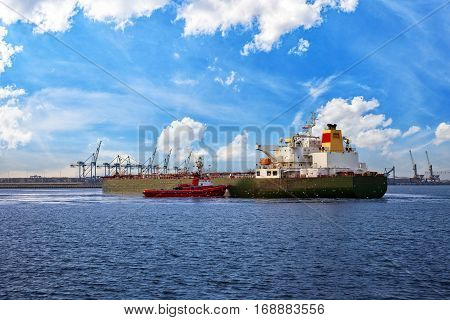 Tug boat towing a tanker ship in port.