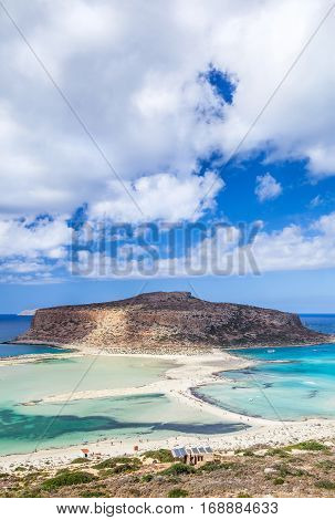 Picturesque view of Balos bay on Crete island Greece. Tourists relax and bath in crystal clear azure water of Balos beach.