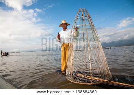 Inle Lake Myanmar - 2017 January 2 : A fisherman posing on his boat with a traditional conical net used on the Inle Lake in central Burma