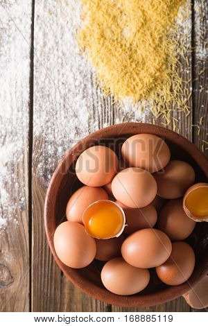 Brown eggs and broken eggs in a brown ceramic bowl on wooden table. Rustic Style. Eggs. Were scattered flour on a wooden table. Baking photo concept . Vermicelli pasta. egg pasta