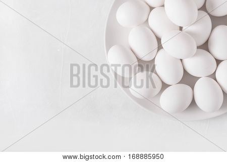 White eggs on a white plate on a white background. Eggs. Easter photo concept. Copyspace