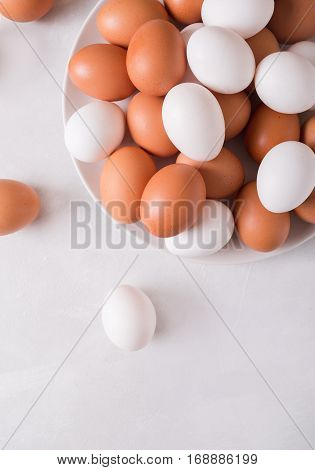 Brown and white eggs on a white plate on a white background. Eggs. Easter photo concept. Copyspace