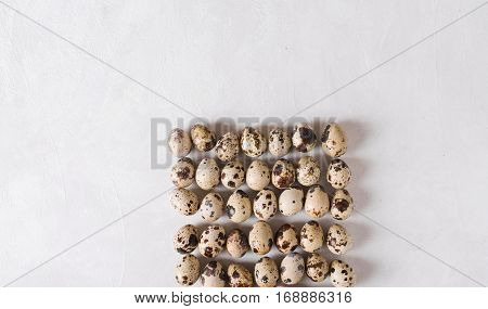 Quail eggs. Quail eggs in the shape of a square on a light background. Easter photo concept. Copyspace